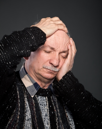 Elderly man suffering from a headache and toothache Stock Photo
