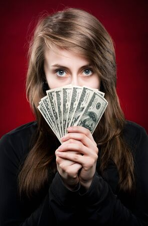 Pretty woman holding fan made of money and contemplating Stock Photo - 13663979