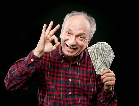 Happy elderly man showing fan of money and sign OK with fingers photo