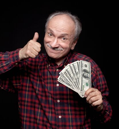 Happy elderly man showing fan of money and sign OK with fingers Stock Photo - 13742209