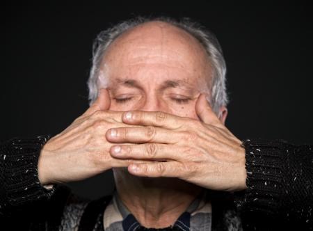boca cerrada: Un anciano con los ojos cerrados cerr� la boca con las manos. Centrarse en las manos