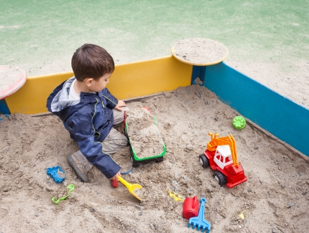 Cute boy in jacket playing in sandbox with a lot of sand toys Banco de Imagens