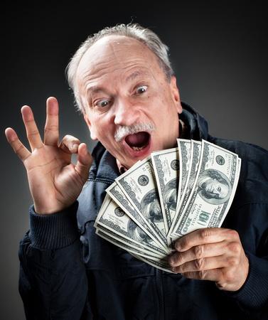 dinero: Anciano feliz mostrando fan de dinero y el signo de OK con los dedos. Centrarse en el dinero. Un hombre de la cara borrosa Foto de archivo