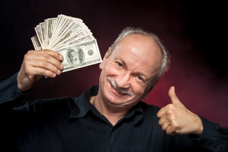 Happy elderly man showing fan of money and sign OK with fingers Stock Photo - 13979022