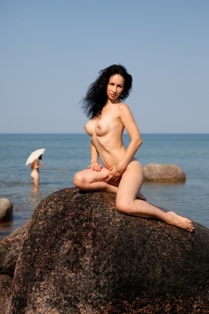 nude woman sitting: Beautiful nude woman sitting on a rock against the sea and blue sky