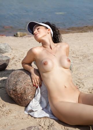 Beautiful young nude woman sunbathing on the beach Stock Photo - 14025511