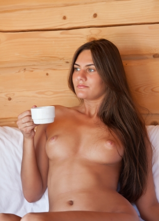 nude in bed: Young nude woman drinking coffee in bed in a camping