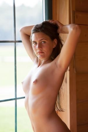 desnudo: Mujer desnuda posando junto a la ventana en el camping