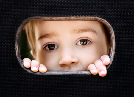 pry: Curious kid spying through the hole in the wooden wall on playground