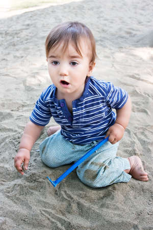 emotive: Cute emotive kid playing with toy and sand on playground