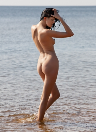 Nude sunbathing woman standing on the sea Stock Photo
