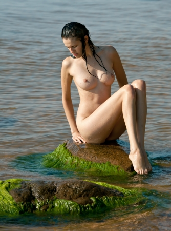 nude woman sitting: Wet naked and sexy girl sitting on stone by the sea Stock Photo