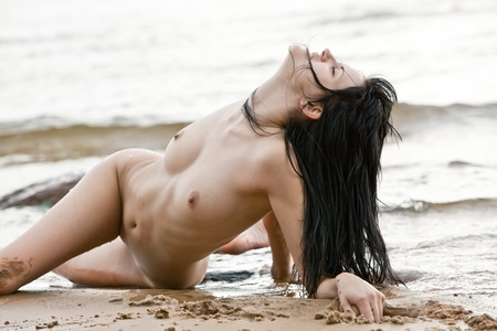 Sexy nude woman lying on the sand near water at beach