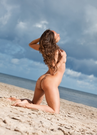 Young nude woman sunbathing on the beach