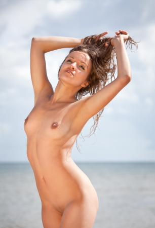 mujer desnuda senos: Joven mujer desnuda tomando el sol en la playa