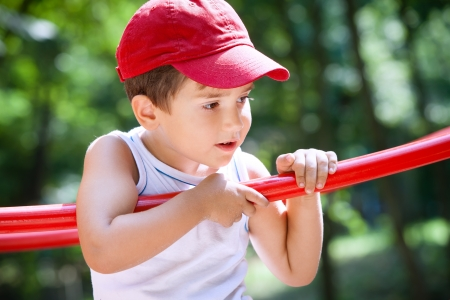 3-4 years old boy standing on a playground in a red cap on the blurred natural background photo