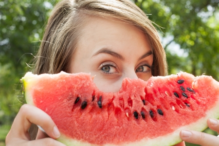 Young woman with watermelon outdoors
