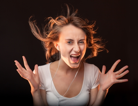 Beautiful Woman Listening Music and screams on a dark background photo
