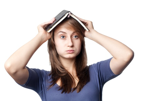 Education. Tired girl holds a notebook on her head on a white background photo