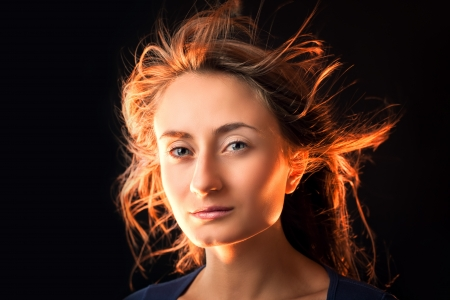 Portrait of a beautiful young woman with hair flying on dark background photo
