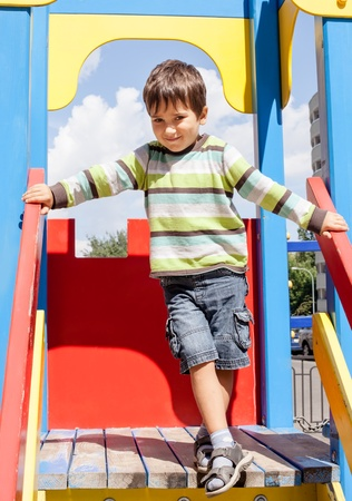 cute boy standing on playground photo