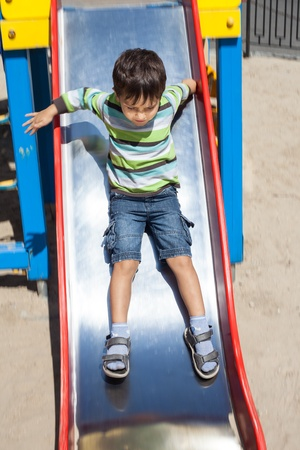 Cute boy  playing on slide photo