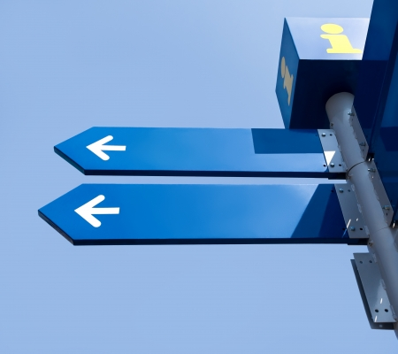Blank directionele verkeersborden over blauwe hemel