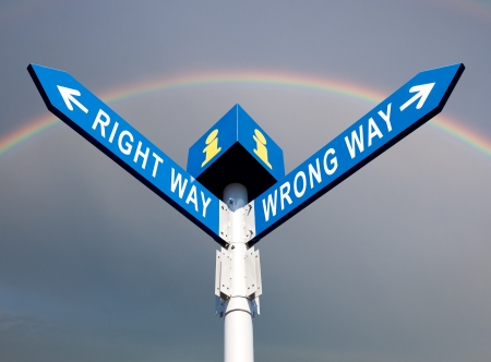 Wrong Way y Way Traffic Sign derecho en el fondo del arco iris photo