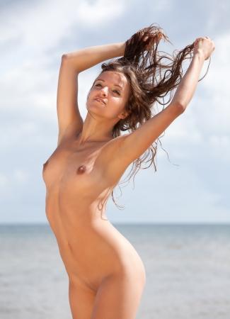 Joven mujer desnuda tomando el sol en la playa Foto de archivo - 15782676