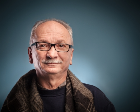 An elderly man with glasses looks skeptically photo