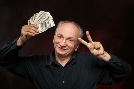 Lucky old man holding group of dollar bills and fingers in victory sign Stock Photo - 15783251
