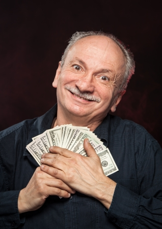 money in hand: Lucky old man holding with pleasure group of dollar bills