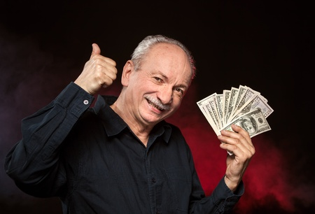 Lucky old man holding group of dollar bills and show OK sign Stock Photo - 15783249