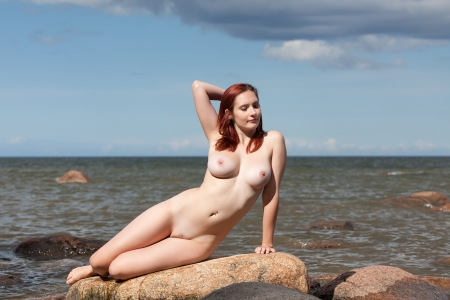 nude outdoors: Young nude woman sitting on stone against the sea background