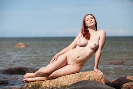 Young nude woman sitting on stone against the sea background