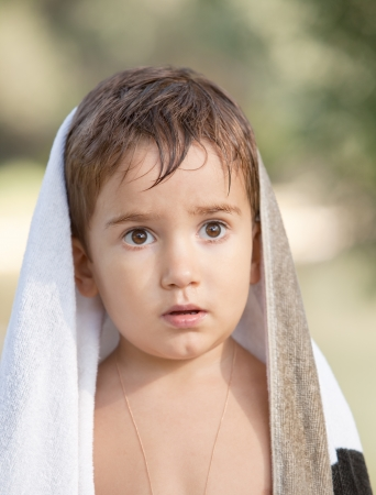 Portrait of a three year old boy with a seus expression on his face and a towel on his head Stock Photo - 15866239