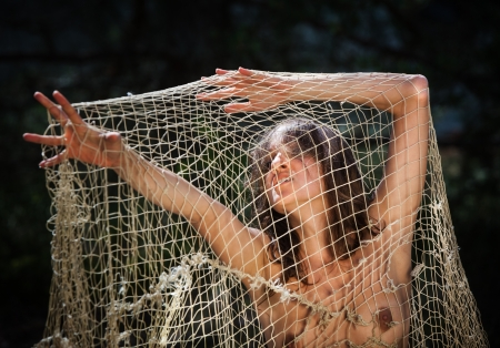 Woman in despair comes out of the net Stock Photo - 15970016