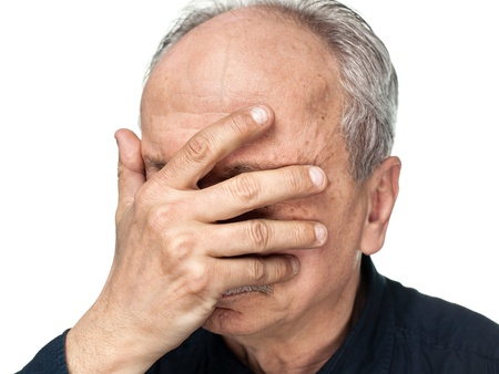 Pain. Elderly man covers his face with hand photo