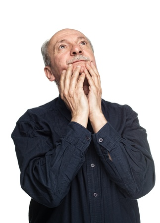 Elderly man with hands near his face  looking up thinking Stock Photo - 16086888