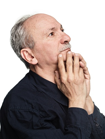 Elderly man with hands near his face  looking up thinking