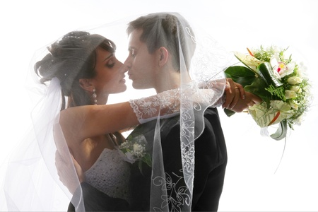 Wedding portrait of kissing just married young couple of groom and bride photo