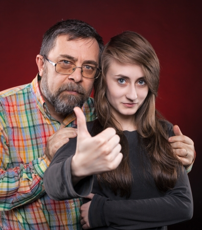 Studio portrait of a father and daughter. Show OK symbol photo