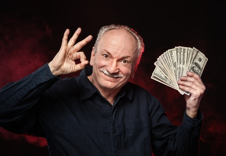 Lucky old man holding with pleasure group of dollar bills Stock Photo - 16367243