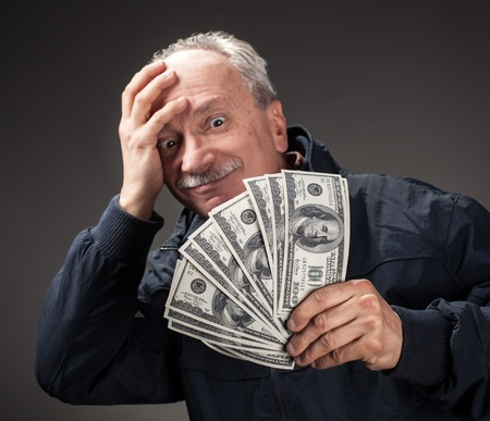 Lucky old man holding with pleasure group of dollar bills. Focus on money Stock Photo - 16367214