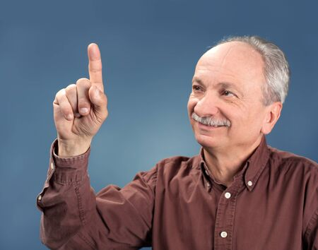 concur: handsome old man pointing up on blue background Stock Photo