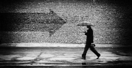 Verkeerde manier. Een man met paraplu. Conceptueel beeld, film grain toegevoegd Stockfoto