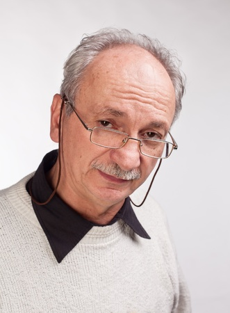 Portrait of a happy mature man with glasses and a white sweater Stock Photo - 16707627