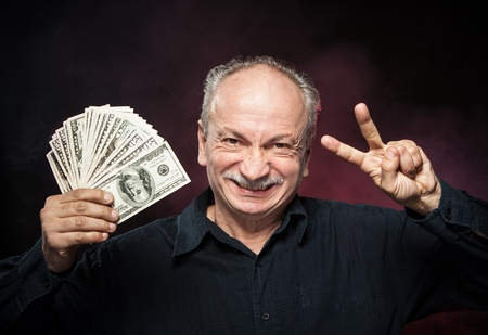 Lucky old man holding with pleasure group of dollar bills. Focus on face Stock Photo - 16909203