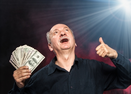 Lucky old man holding with pleasure group of dollar bills. Focus on face Stock Photo - 16909205