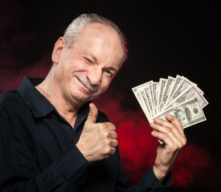 Lucky old man holding with pleasure group of dollar bills Stock Photo - 16909204